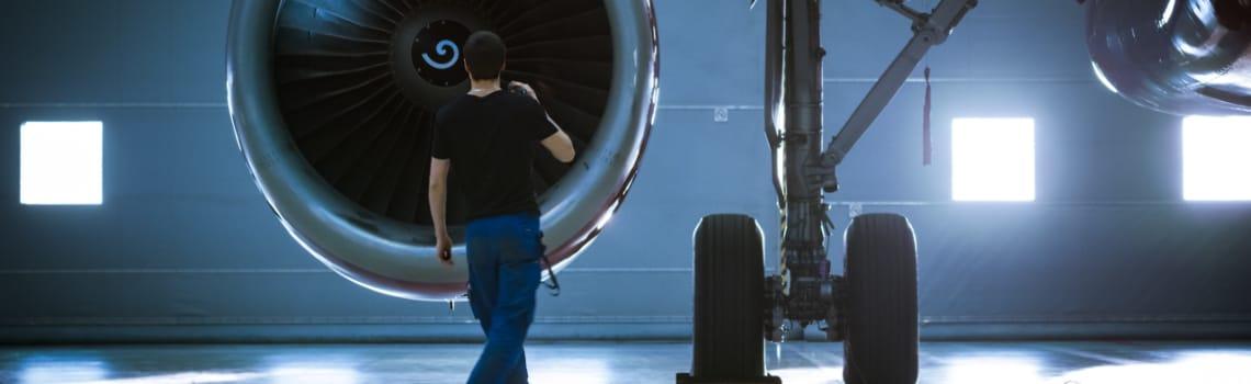 mann steht vor flugzeugturbine fuer wartung